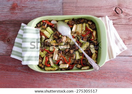 Delicious assorted fresh roast vegetables in an oven dish with kitchen cloth and serving spoon on a wooden table, high angle view - stock photo