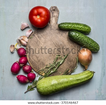 Delicious assortment of farm fresh vegetables around a round cutting board place for text,frame on wooden rustic background top view close up - stock photo