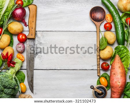 Delicious assortment of farm fresh vegetables with knife and spoon on white wooden background, top view. Vegetarian ingredients for cooking. Healthy cooking concept. - stock photo