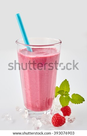 Delicious autumn raspberry smoothie made from fresh fruit blended with yogurt and served in a long glass on ice for a refreshing drink - stock photo