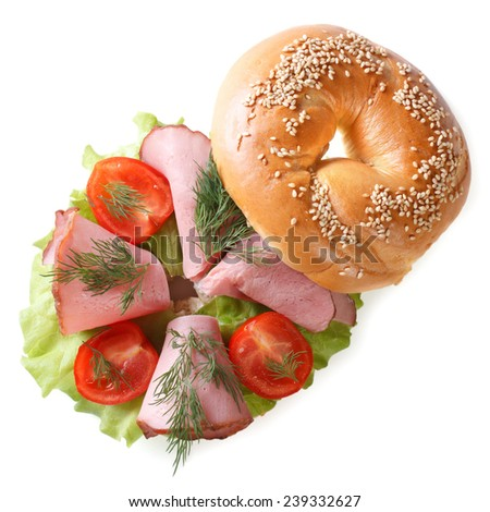 delicious bagel with ham and vegetables isolated on a white background close-up. top view  - stock photo