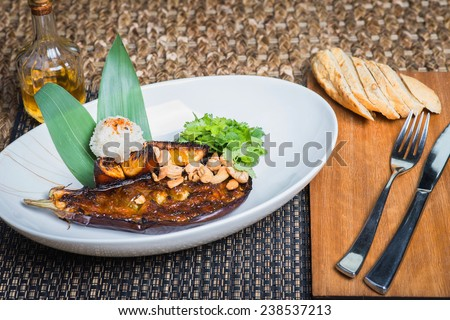 delicious baked eggplant on a plate with nuts and boiled rice, bun and devices on a table at restaurant - stock photo