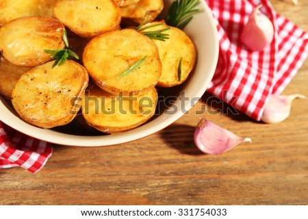 Delicious baked potato with rosemary in bowl on table close up - stock photo