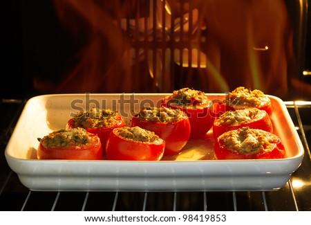 Delicious baked stuffed tomatoes with meat and vegetables in the oven - stock photo