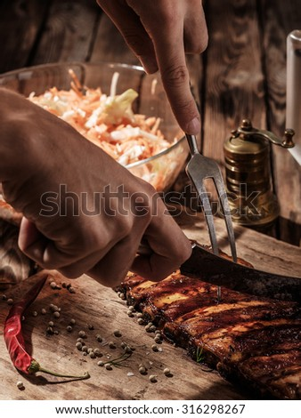 Delicious BBQ ribs with coleslaw on wooden table. Chef cut up barbecue ribs. - stock photo