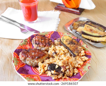 Delicious beef meatballs and asian rice with carrot and dried fruits served on a color plate.Grilled eggplants with garlic and tomato juice in the blurred background. Homemade cooking.Selective focus  - stock photo