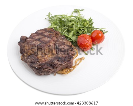 Delicious beef steak with arugula, onion rings  and cherry tomatoes.  Isolated on a white background. - stock photo