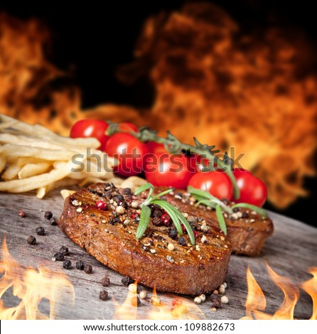 Delicious beef steaks with vegetable on wooden table - stock photo