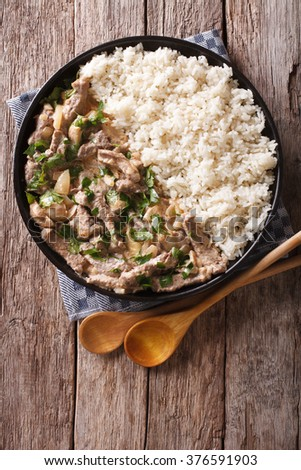 Delicious beef stroganoff with mushrooms and rice close-up on a plate on the table. vertical view from above