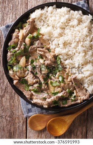 Delicious beef stroganoff with rice close-up on a plate on the table. Vertical view from above