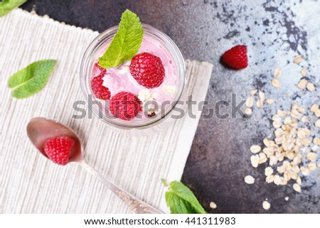 Delicious berry smoothie yogurt with oat flakes and mint leaves for breakfast. Jar with milkshake with raspberries, green straw and silver spoon on the table. Delicious and healthy breakfast - stock photo