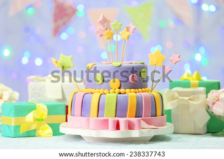 Delicious birthday cake on shiny light background - stock photo