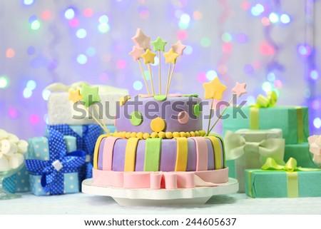 Delicious birthday cake on shiny light background - stock photo