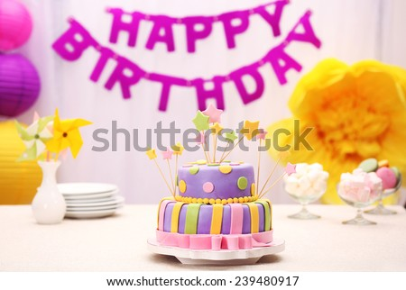 Delicious birthday cake on table on bright background - stock photo