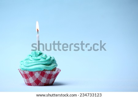 Delicious birthday cupcake on table on light blue background - stock photo