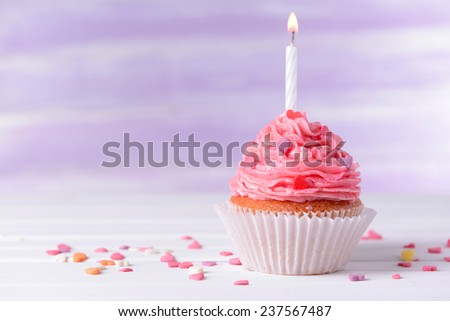Delicious birthday cupcake on table on light purple background - stock photo