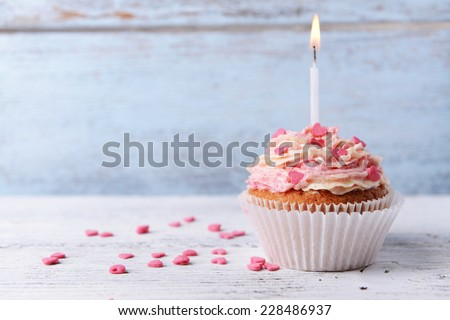 Delicious birthday cupcake on table on wooden background - stock photo