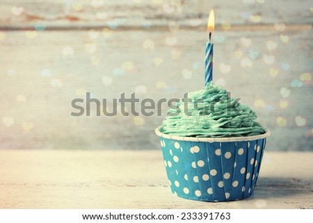 Delicious birthday cupcake on wooden table - stock photo