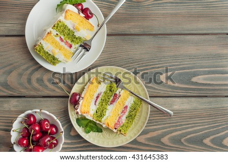Delicious biscuit cake with cherries and strawberries on wooden background - stock photo