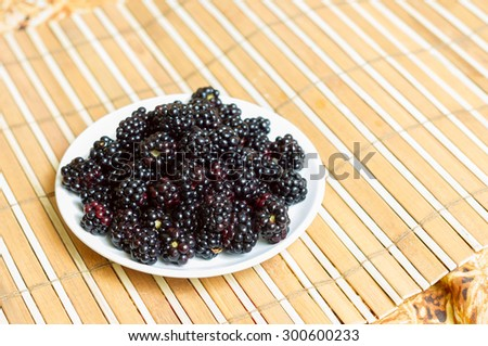 Delicious blackberry on a white plate on the table - stock photo