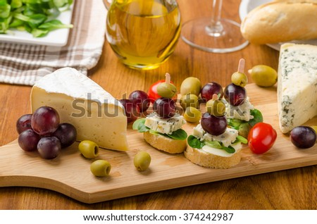 Delicious blue cheese with olives, grapes and salad, behind wine, olive oil, baquettes - stock photo