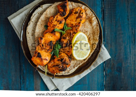 Delicious boneless chicken kebab on skewer served on arabic pita bread. - stock photo