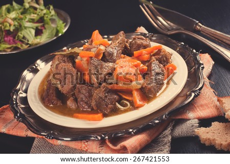 Delicious bourguignon beef stew on white plate. Selective focus. Retro style toned.   - stock photo
