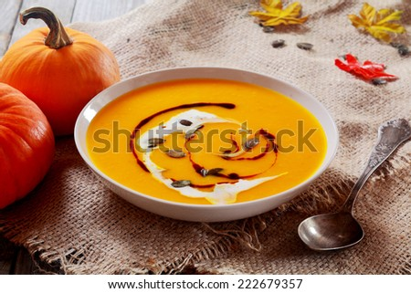 Delicious bowl of autumn or fall pumpkin soup garnished with cream and pumpkin pips on rustic burlap with two fresh pumpkins alongside - stock photo