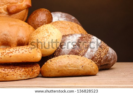 delicious bread on wooden table on brown background - stock photo