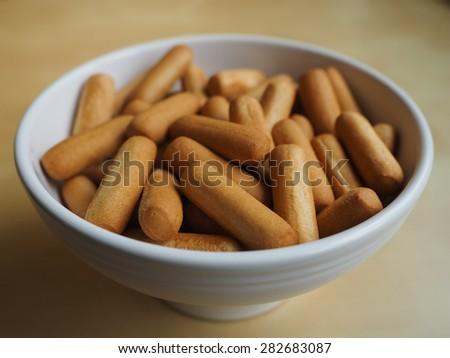 Delicious bread sticks in white bowl - stock photo