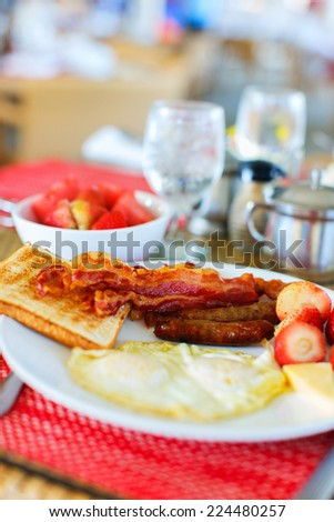 Delicious breakfast an omelet, vegetables, bacon and toast - stock photo
