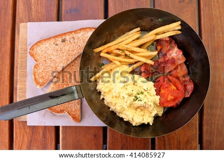 Delicious breakfast - bacon,scrambled eggs, grilled tomato and fries in a pan, with toast on the side - stock photo