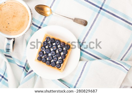 Delicious breakfast of blueberry cake and coffee in vintage cup with a spoon - stock photo