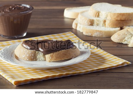 Delicious breakfast of bread with chocolate cream on a yellow checkered napkin. A bowl and a plate. - stock photo
