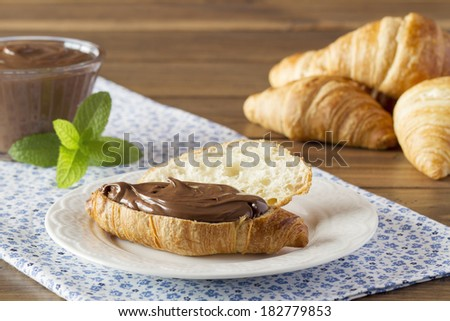 Delicious breakfast of croissant with chocolate cream on a blue napkin. A bowl, a plate and mint. - stock photo
