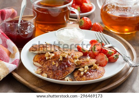 Delicious breakfast. Pancakes with fresh strawberries and cream, jam and tea, close-up - stock photo