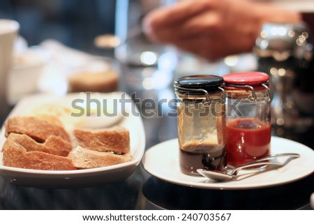 Delicious breakfast, toasts and fruity jam in jars on the plates - stock photo