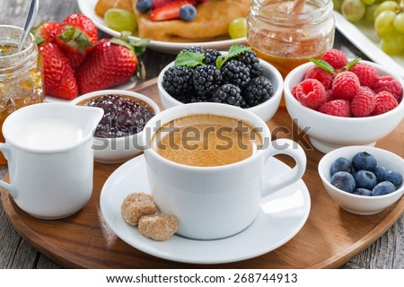 delicious breakfast with coffee, fresh berries and pancakes, horizontal - stock photo