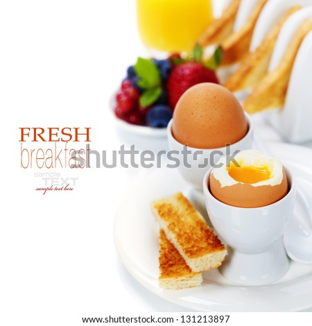 Delicious breakfast with eggs, fresh toasts, fructs and juice (with easy removable text) - stock photo