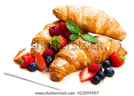 Delicious breakfast with fresh croissants and ripe berries on white background - stock photo
