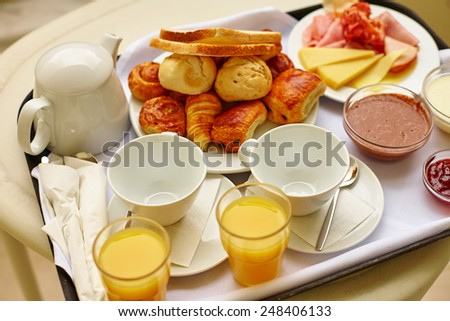Delicious breakfast with fresh orange juice and pastry, focus on coffee cups - stock photo