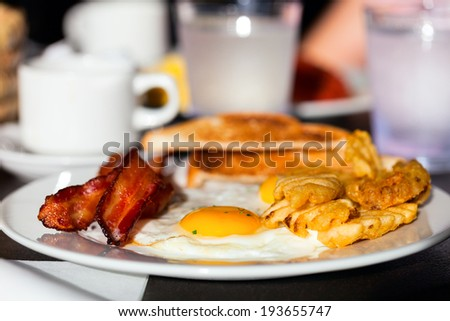 Delicious breakfast with fried eggs, vegetables, bacon and toast - stock photo