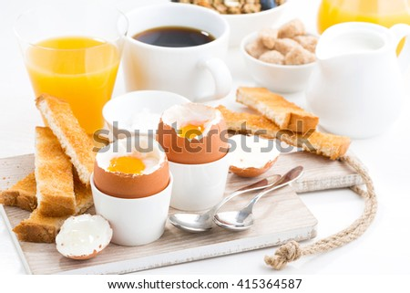 delicious breakfast with soft boiled eggs and crispy toasts, closeup - stock photo