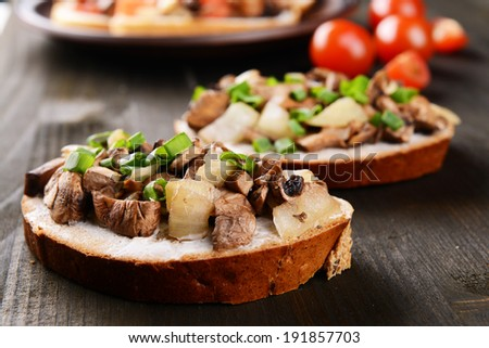 Delicious bruschetta with mushrooms on table close-up - stock photo