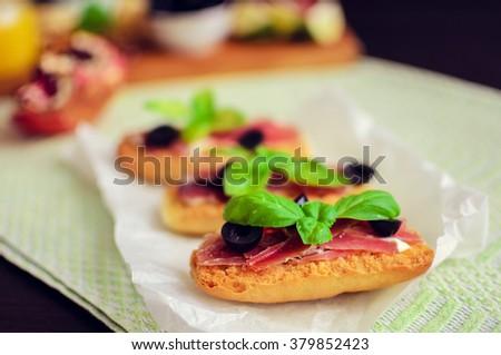 Delicious bruschetta with prosciutto, olives and basil. Italian bruschetta sandwich Close Up. Italian appetizer. Selective focus. - stock photo