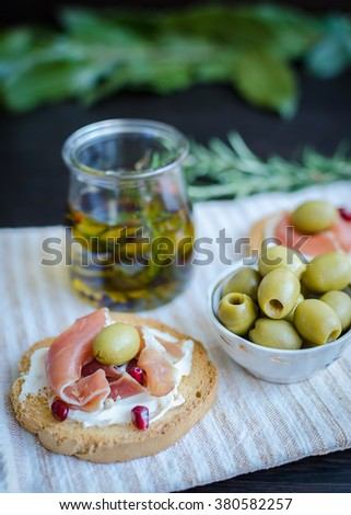 Delicious bruschetta with prosciutto, olives and pomegranate on background of olive oil with spices. Italian bruschetta sandwich. Close Up. Italian appetizer. Selective focus. - stock photo