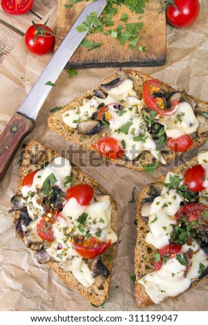 delicious bruschetta with tomatoes, cheese and mushrooms - stock photo