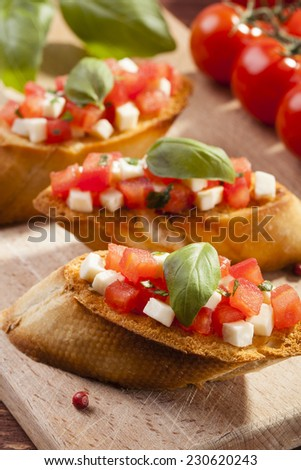 Delicious bruschetta with tomatoes, mozzarella and herbs - stock photo