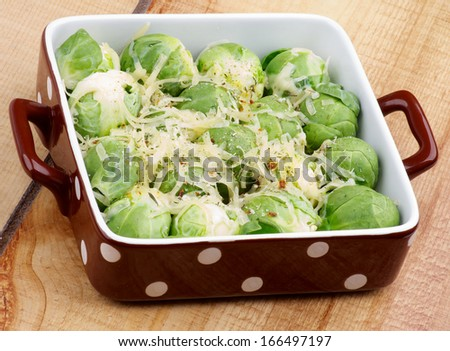 Delicious Brussels Sprouts Casserole with Grated Cheese and Spices in Brown Polka Dot Bowl closeup on Wooden background - stock photo