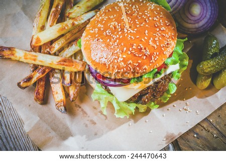 Delicious burger and chips, hand-made in the house on rustic table - stock photo